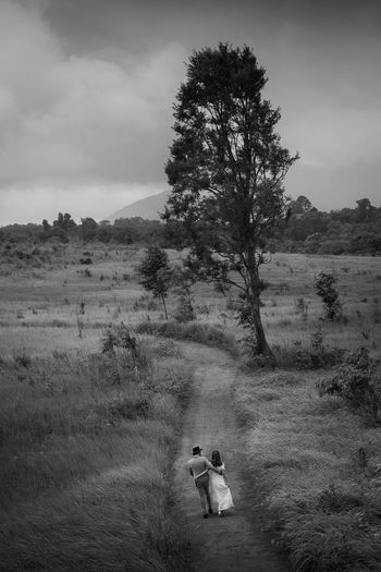 Rear view of couple walking on land against sky