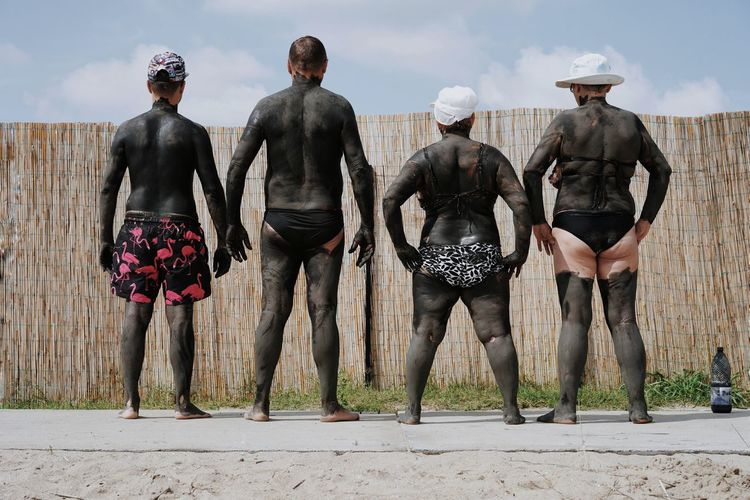 Rear View Of Friends Covered In Mud At Beach