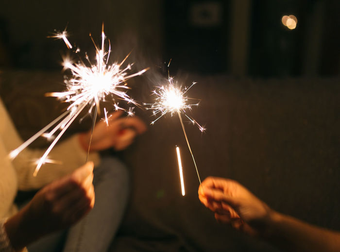Cropped image of women holding sparklers
