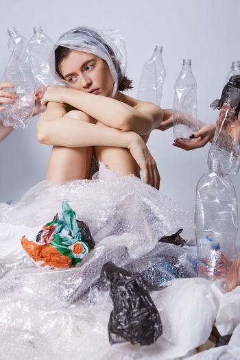 Thoughtful young woman sitting amidst plastics