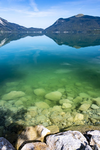 Stones and transparent colorful lake water against the mountains and their mirroring