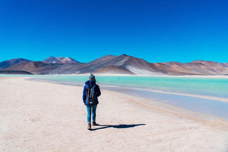 Full length of man walking in desert against clear blue sky