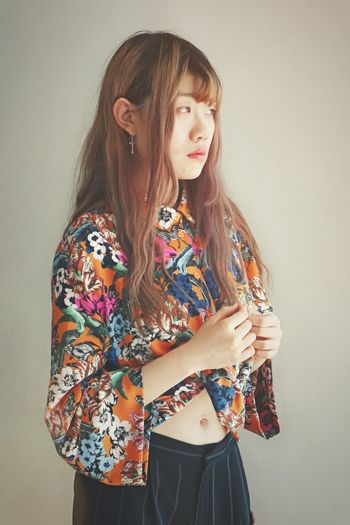 Fashionable Young Woman Standing Against Wall