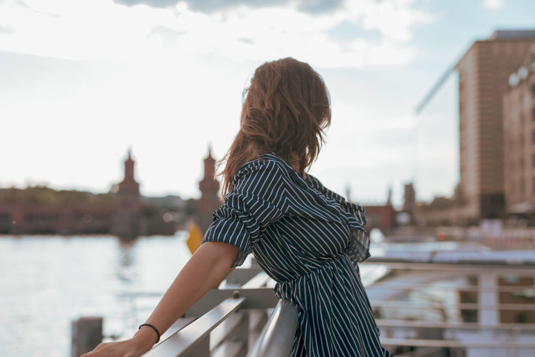 Side view of woman standing by railing in city