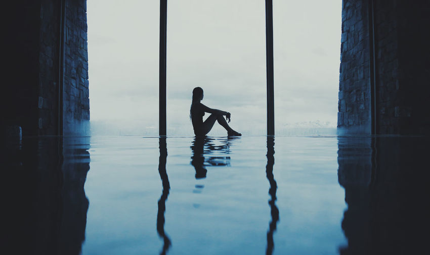 Woman sitting at infinity pool in city