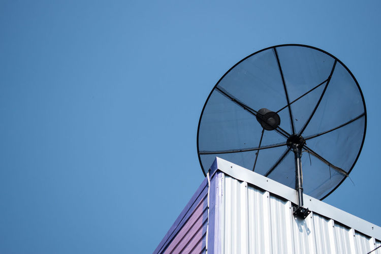 Low angle view of satellite dish against clear blue sky