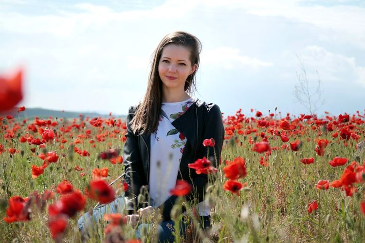 Portrait of young woman standing by poppy flowers on field against sky