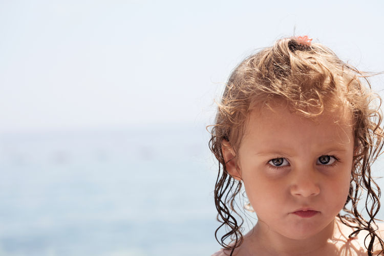 Angry little girl on a family beach holiday Babies Only Baby Beach Blond Hair Child Childhood Close-up Curly Hair Cute Day Focus On Foreground Headshot Horizon Over Water Human Body Part Innocence Looking At Camera One Person Outdoors Portrait Real People Sea Sky Summer Vacations Water The Portraitist - 2018 EyeEm Awards