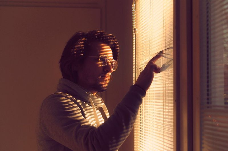 Mid Adult Man Looking Through Window At Home