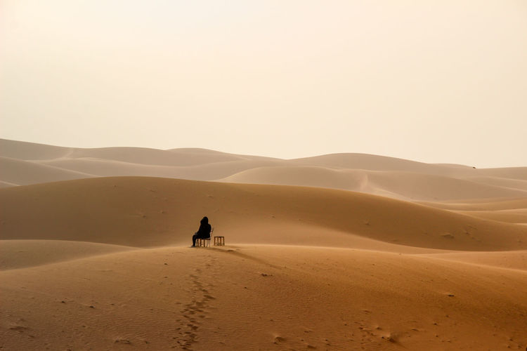 Full length of woman on sand dune in desert against sky