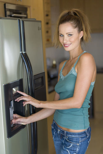 Woman filling glass at the water dispenser of the refrigerator Refreshment Adult Appliance Beautiful Woman Casual Clothing Cold Drink Domestic Life Domestic Room Glass Home Household Equipment Indoors  Jeans Kitchen Lifestyles Looking At Camera One Person Portrait Refrigerator Smiling Standing Water Water Dispenser Women Young Women