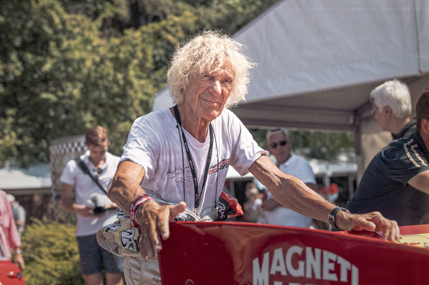 Racing legend Arturo Merzario at the Classic Days, 2018, Schloss Dyck, pushing his Alfa Romeo Tipo 33TT12 into the paddock. He is famous for being the first one to save Niki Lauda from his burning wreck at his crash during the Grand Prix 1976 on the Nürburgring. Arturo Merzario Classic Cars Classic Days 2018 Classic Days Schloss Dyck Casual Clothing Emotion Formula 1 Driver People Racing Drivers Racing Legends Senior Adult Senior Men