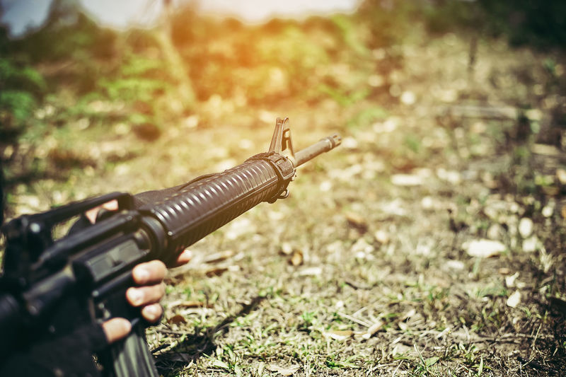 Cropped image of military office aiming weapon on field
