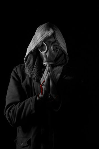 Close-up of a man wearing gas mask over black background