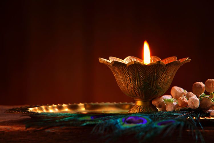 Close-Up Of Oil Lamp And Peacock Feather On Wooden Table Against Black Background