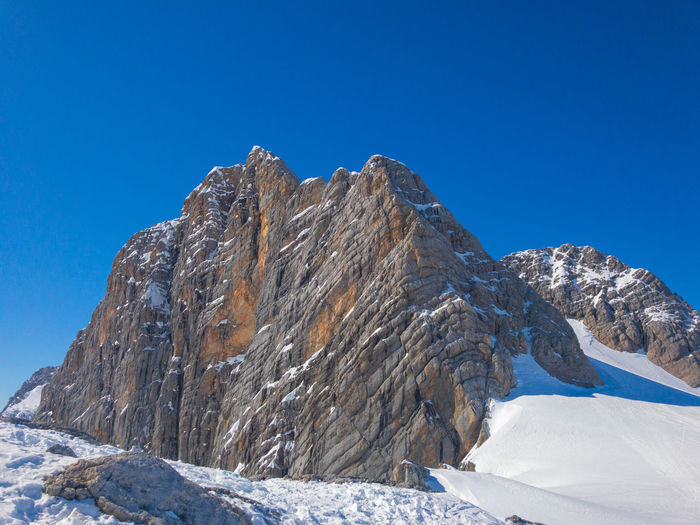 Low angle view of snowcapped dachstein against clear blue sky