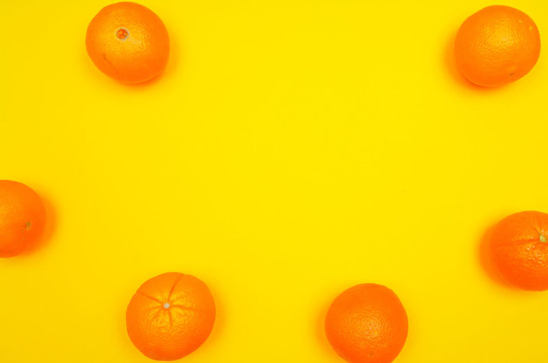 Close-up of orange fruits over colored background