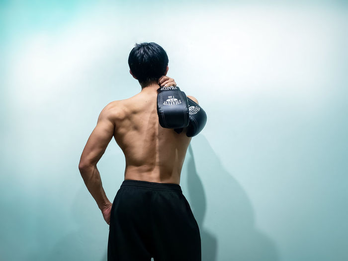 Rear View Of Shirtless Mid Adult Man Holding Boxing Gloves While Standing Against Wall