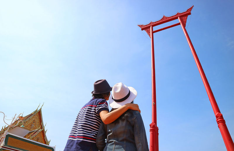Couple looking up to the amazing giant swing or sao ching cha, in old city of bangkok, thailand