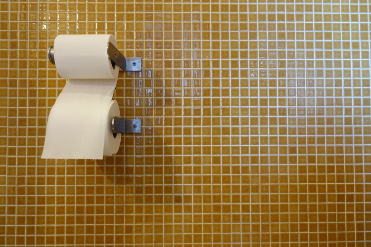 Close-up of toilet papers on tiled wall