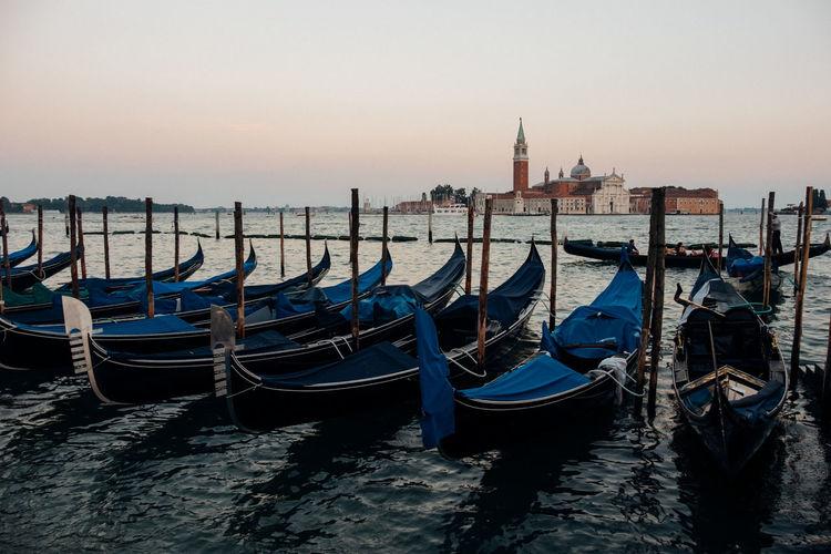 Gondolas moored on sea during sunset