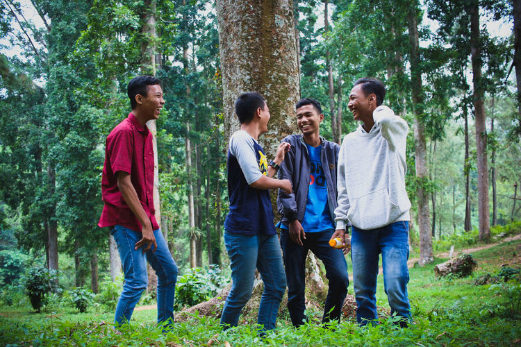 Happy friends talking against trees in forest