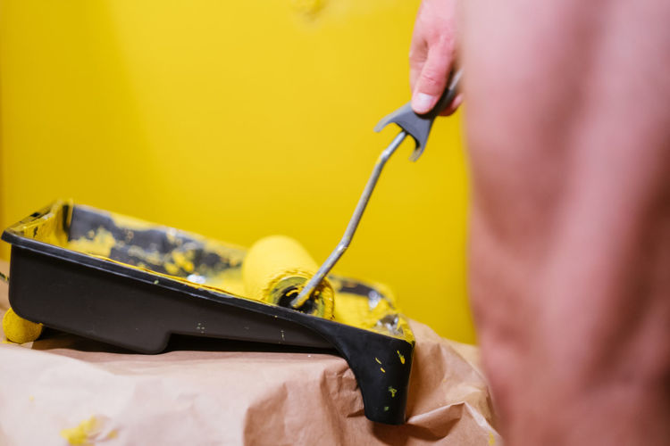 Close-up of person working on yellow machine