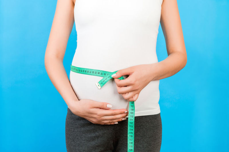 Midsection of woman holding blue while standing against wall