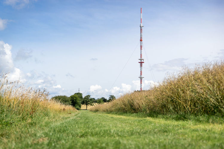 Scenic view of field by communications tower against sky