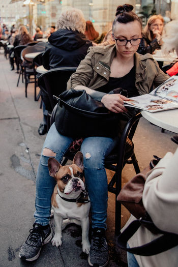 Streetwise Photography Domestic Animals Real People Domestic Pets Dog One Animal Canine Mammal Sitting Group Of People Lifestyles People Incidental People Women Casual Clothing Adult Seat Men Pet Owner Warm Clothing Vienna Streetphotography Bulldog The Art Of Street Photography The Street Photographer - 2019 EyeEm Awards