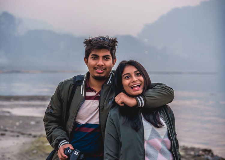 Beauty In Nature Bonding Brother & Sister Casual Clothing Day Focus On Foreground Front View Happiness Leisure Activity Lifestyles Looking At Camera Love Mountain Nature Outdoors Portrait Real People Sea Smiling Standing Togetherness Two People Water Young Adult Young Men Young Women