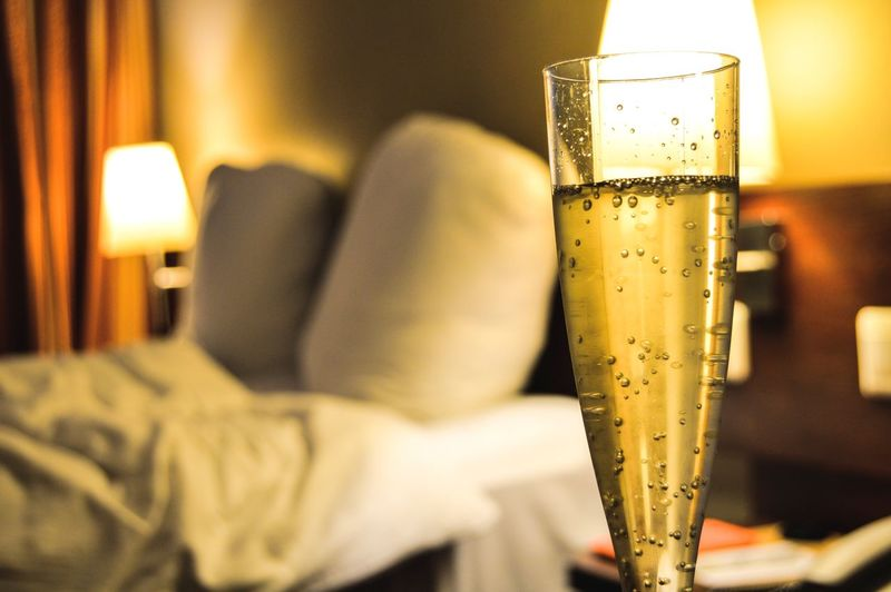 Close-Up Of Champagne Glass In Illuminated Hotel Room