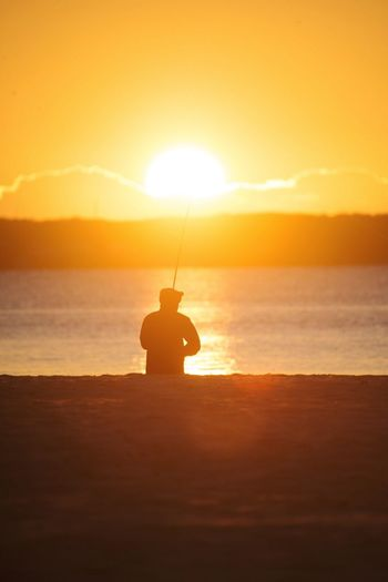 Fisherman at Sunrise Sunset Water Sea Scenics Silhouette Tranquil Scene Tranquility Vacations Sun Idyllic Sky Beauty In Nature Nature Orange Color Glowing Ocean Summer Vibrant Color Calm Hobbies