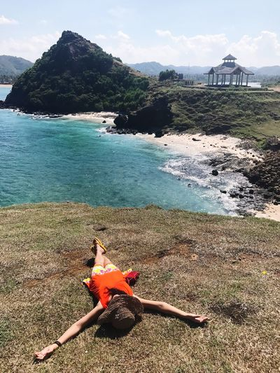 High angle view of woman lying on cliff against sea