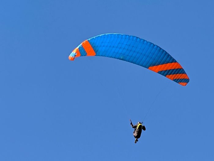 High in the blue sky! Paragliding. Minimalism. Red Blue Sky Background Extreme Sports Sport Flying Stripes Hanging Yellow Harness Cables Dangerous Therapeutic Wind Motion Tilted Paragliding Stunt Person Parachute Extreme Sports Pilot Flying Sport Adventure Headwear Multi Colored Sports Activity Safety Harness Gliding