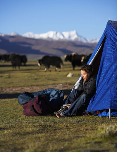Man relaxing on tent on field against sky