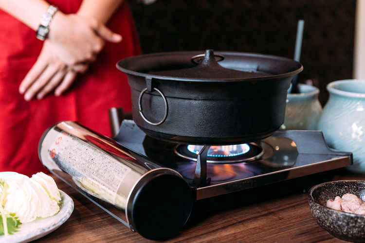 A woman wearing kimono is waiting for Sukiyaki black color hot pot boiling. Food And Drink Appliance Food Kitchen Utensil Preparation  Stove Household Equipment Indoors  Table Human Hand Midsection Hand Focus On Foreground Wood - Material One Person Holding Freshness Cooking Pan Heat - Temperature Preparing Food Camping Stove