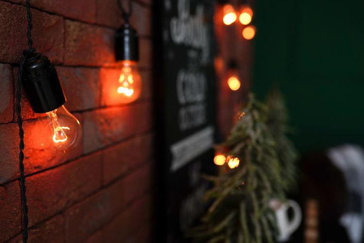 Illuminated christmas lights hanging against wall at night
