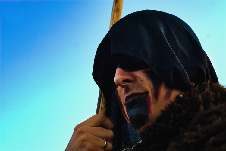 Low angle view of man with face paint wearing costume standing against sky