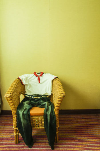 T-shirt and jeans resting on rattan chair against yellow wall in a room filled with natural light Copy Space Emptiness Jeans Natural Light Room Carpeted Floor Chair Concept Day Indoors  No People Rattan Chair Resting T-shirt Trouser Pocket Vertical Yellow Wall Fashion Stories Inner Power Visual Creativity The Still Life Photographer - 2018 EyeEm Awards