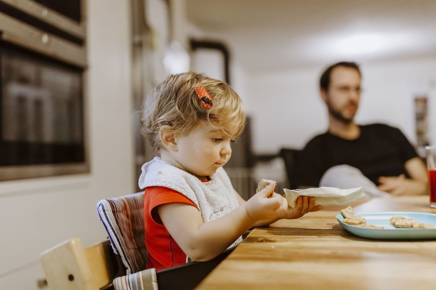 Baby girl unwrapping cookies with father in background – Germany Baby Cookies Eating Man Baby Babygirl Bib Child Childhood Domestic Life Family Family With One Child Father Food High Chair Home Interior Indoors  Kitchen Portrait Sitting Table Togetherness Two People Unhealthy Eating Unwrapping
