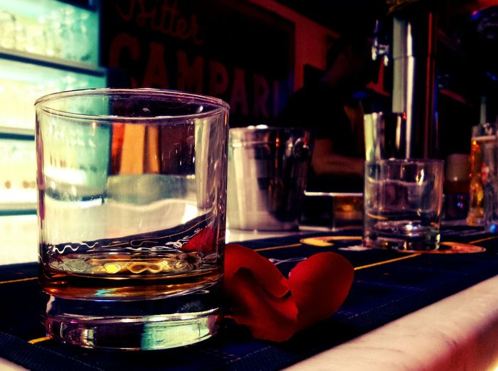 Close-up of scotch whisky in glass with red rose petal on bar counter at nightclub