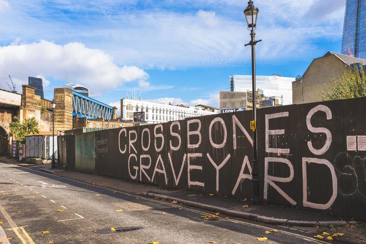 Graffiti on road against sky in city