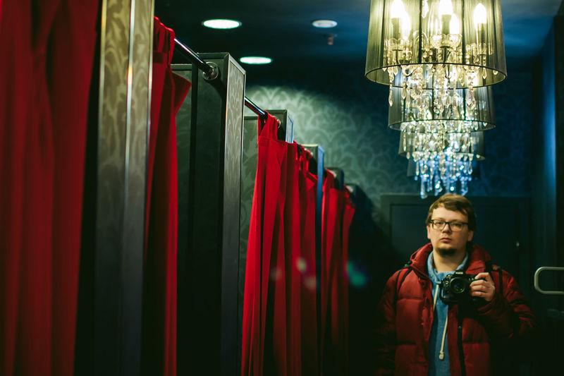 Portrait of man with camera standing in illuminated corridor