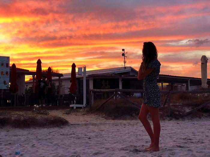 Full length of woman standing at beach against orange sky