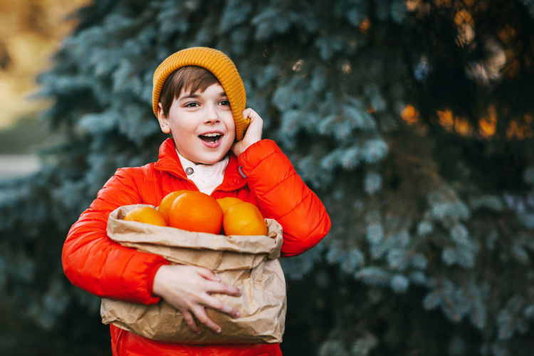 A boy in a bright orange jacket and a yellow hat holds a large package with oranges