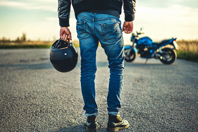 Low section of man holding helmet while standing on road