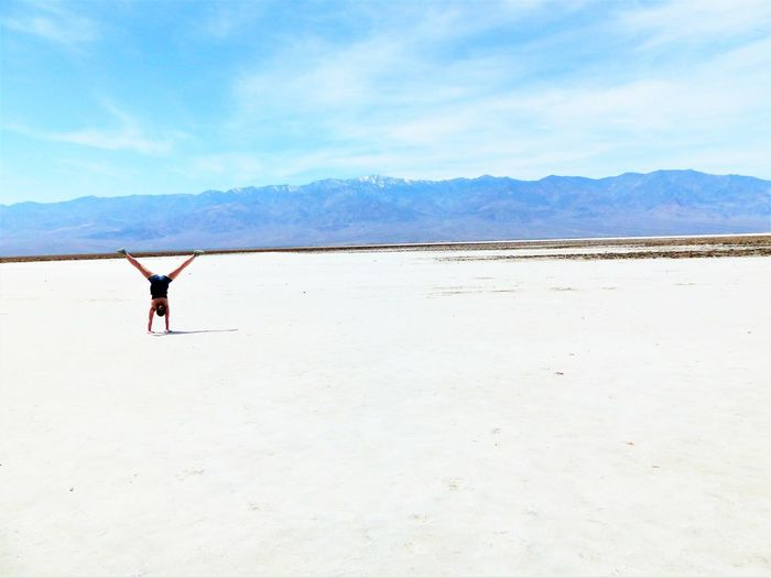 Full length rear view of woman doing cartwheel in desert against sky