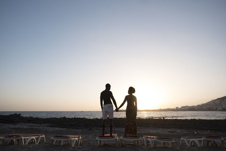 Couple standing at beach against sky during sunset