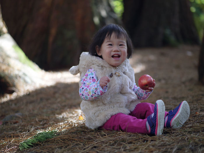 Portrait Of Cheerful Baby Girl Holding Apple While Sitting On Field